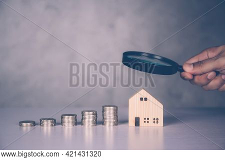 Hands Of Businessman Holding Magnifying Glass Home Model With Search Real Estate And Property Invest