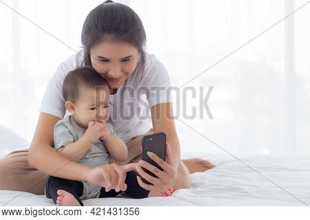 Young Asian Mother And Little Baby Girl Or Newborn Selfie With Smart Phone On Bed In Bedroom, Happin