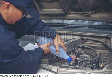 Car Mechanic Man Hands Pouring Deionized Purified Distilled Water For Car Battery Mechanical Service