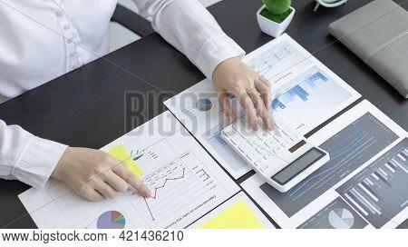 Young Asian businesswoman presses a calculator to calculate income tax and corporate income in a pri