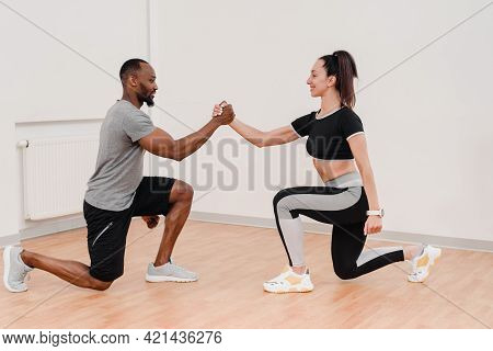 Happy Multinational Couple Stretching Together During Fitness Training