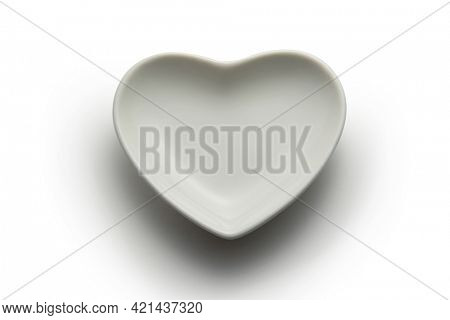 Empty ceramic saucer in the form of heart on white background