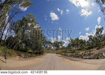 Causeway Over A Country Creek Under A Cloudy Blue Sky, Landscape Curved With Fish Eye Lens
