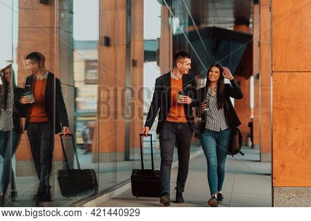 Business man and business woman talking and holding luggage traveling on a business trip, carrying fresh coffee in their hands.Business concept