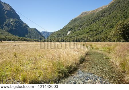 Stream Leading Through Flat Grassed Scenic Plains Stretching In Distance Bordered By Converging Moun