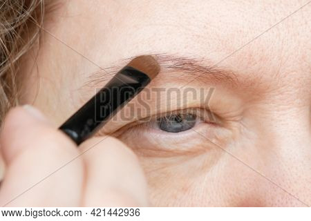 Middle-aged Woman Does Corrective Eye Makeup To Correct The Drooping Eyelid. Ptosis Is A Drooping Of
