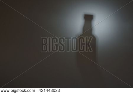 Bottle In The Light. The Blurry Silhouette Of A Whiskey Bottle. Defocused Shadow With Noise. Abstrac