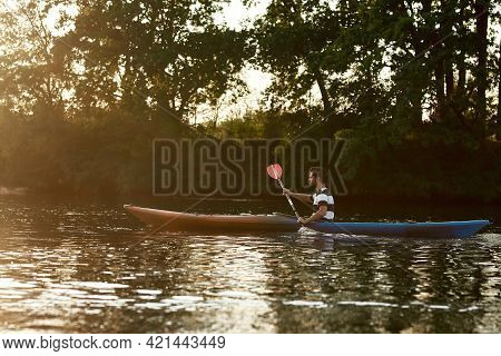 Young Man Holding A Paddle, Kayaking In A Lake Surrounded By Nature On A Summer Afternoon. Kayaking,