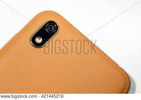 Closeup Of Camera Module On Smartphone Brown.mobile Phone Camera, Flash Lens. Closeup.white Backgrou