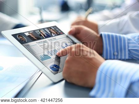 Close Up Of Person Video Conferencing With Colleagues On Digital Tablet, Analyzing Financial Statist