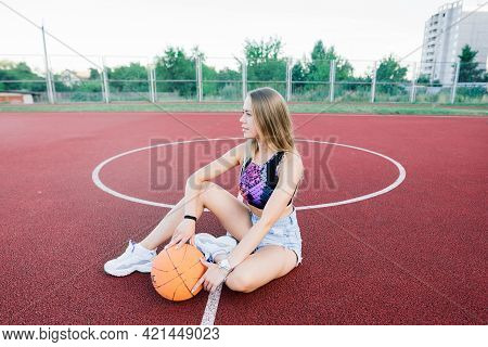 Young Woman With A Basketball On An Outdoor Basketball Court