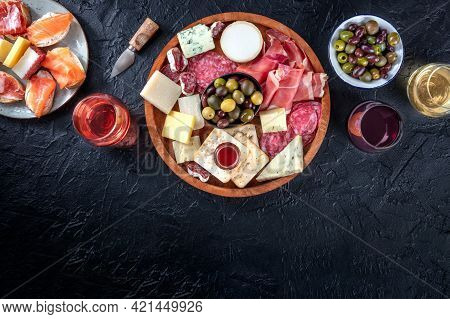 Buffet With Wine And Appetizers On A Black Background. Italian Delicatessen. A Platter Of Snacks Wit