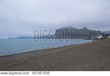 Empty Beach In The Bay Of The Resort Town Of Sudak, Crimea. Off-season. Cloudy Day At The End Of Apr
