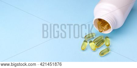 Banner Of Fish Oil Gel Capsules. Omega 3 Fish Oil Capsules Out Open Container On Blue Background Wit