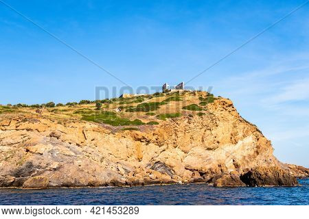 Ancient Ruins Of Temple Of Poseidon On The Cliff, Sounion - Distant View From The Sea In Sunny Summe
