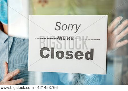 Sign Sorry We Re Closed On Shop Entrance Door As New Normal Shutdown. Woman In Mask Gloves Hangs Clo