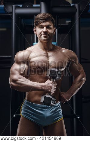 Caucasian Athletic Man Exercising Pumping Up Biceps Muscles. Strong Bodybuilder With Six Pack, Perfe