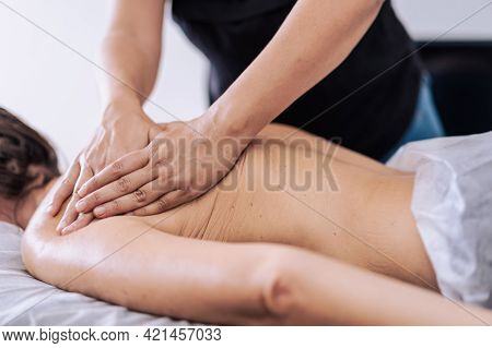 Woman Receiving A Back Massage In A Spa Center. Female Patient Is Receiving Treatment By Professiona