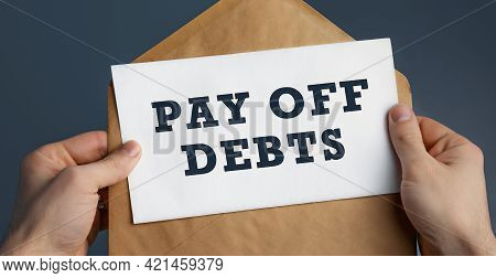 Closeup Of A Male Hands Holding Craft Envelope With Text Pay Off Debts On Blue Background. Communica