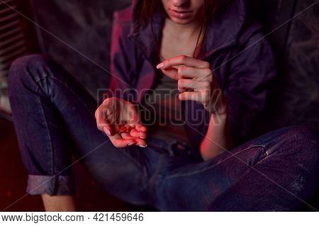 Drug addict female person holds pills, den