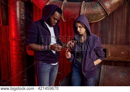 Drug addict man and woman with spoon in den