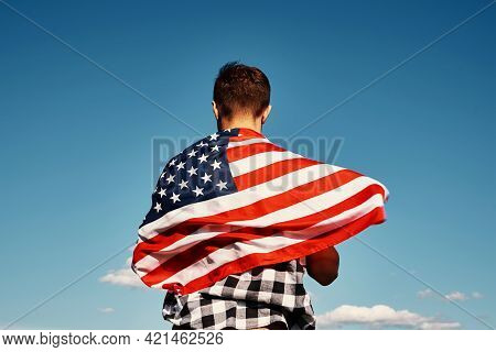 American Flag Outdoors. Man Holds Usa National Flag Against Blue Cloudy Sky. 4th July Independence D