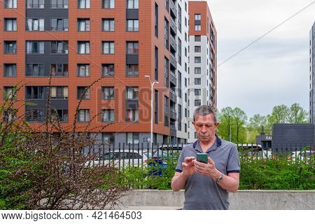 An Adult Caucasian Senior Man In A Gray T-shirt Stands Against The Background Of Residential Buildin