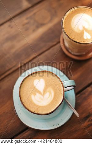 From Above Of Ceramic Cups On Saucers With Freshly Brewed Latte With Hearts On Froth