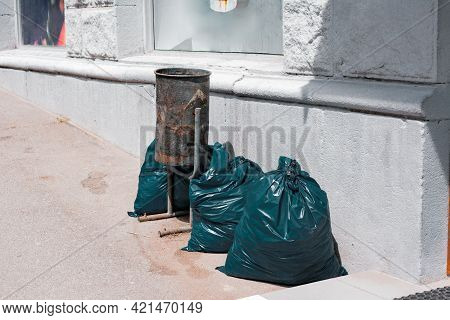 Garbage Bags On The Sidewalk On The Street. Ready For Pick Up. Overflowing. Neighbourhood. Trash Can