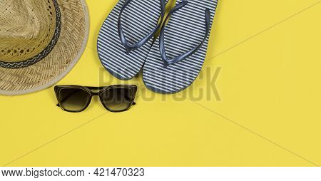 Summer Background. Straw Sun Hat, Sunglasses And Blue And White Striped Beach Slippers On A Yellow B