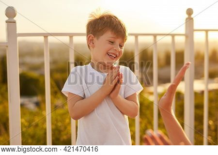 Cheerful Kid Clapping Hands And Laughing While Playing With Crop Parent On Terrace In Summer Morning