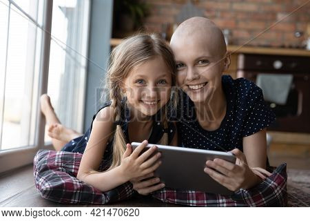 Happy Ill Hairless Young Mother And Pre Teen Daughter