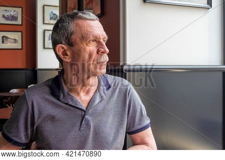 An Adult Caucasian Senior Man In A Gray T-shirt With A Mustache And Wrinkles On His Face Sits At A T