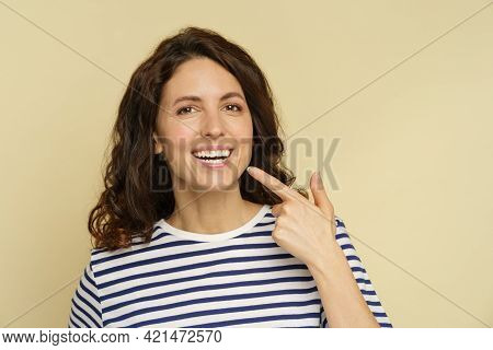 Millennial Woman With Beaming Smile Point Finger To White Healthy Teeth. Closeup Portrait Of Happy F