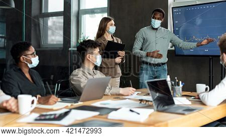 Colleagues Having Meeting In Boardroom, Businessman Showing Graph