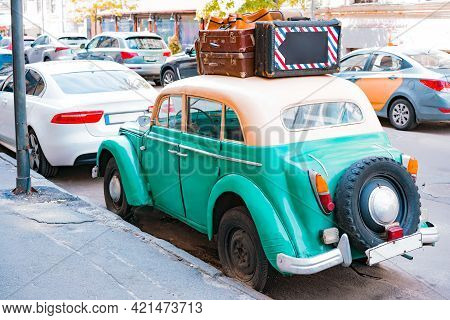 Turquoise Vintage Car With Many Leather Suitcases On The Roof And  And Spare Wheel Stands On The Str