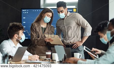 Colleagues Having Meeting In Boardroom, Woman Showing Documenation