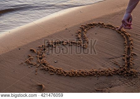 Close Up View Of Woman Hand Drawing Heart With Finger On The Sand At The Beach. Romantic Love Symbol