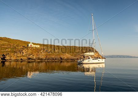Old Whitewashed Abandoned Church Agios Ioannis On Dramatic Cliff With A Sailboat Anchored In A Bay,