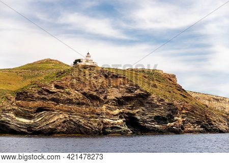 Old Whitewashed Lighthouse Akra Tamelos On Majestic Cliff On Kea Island, View From The Sea With Blue
