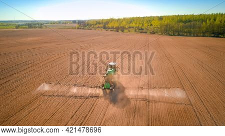 Drone View Of A Tractor Spraying Fertilizers And Chemicals On The Soil In The Spring In A Large Fiel