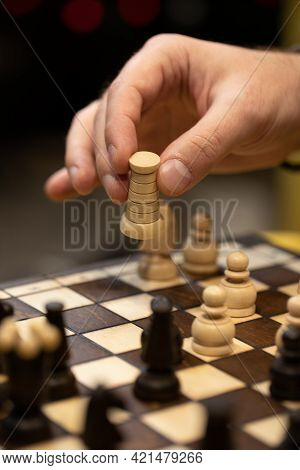 Hand Taking Next Step On Chess Game. Human Hand Moving Wooden White Rook Piece