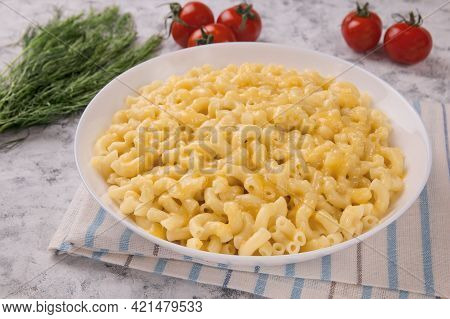 Macaroni And Cheese On A White Plate With Parsley And Cherry Tomatoes On A Gray Background. American