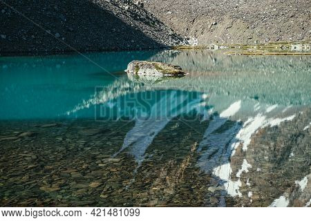 Rock In Turquoise Mountain Lake. Snowy Mountain Reflected In Azure Clear Water Of Glacial Lake. Beau