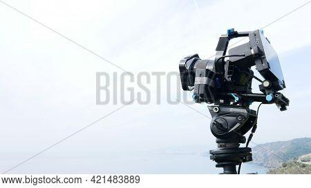 Professional Camera On Tripod Taking Picture Film Video Of Sea Coastal Landscape, Andalucia Spain.