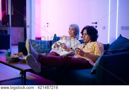 Couple Playing Videogame On Console. Girl Losing And Not Letting The Guy Play Normally By Closing Hi