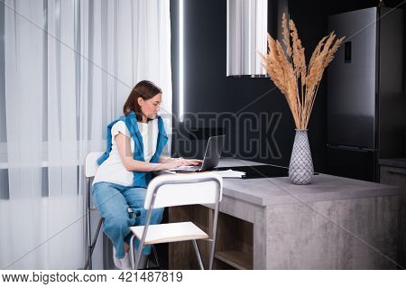 Happy Young Beautiful Woman Using Laptop Working Remotely While Sitting At Home Kitchen.