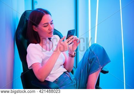 Girl Relaxing Playing Games On Mobile Phone And Sitting On A Gaming Chair. Room With Colorful Neon L