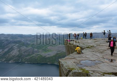 Rogaland, Norway - 23rd May, 2017: Hikers Being Brave And Taking Pictures While Posing On The Edge O
