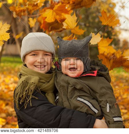 Happy Brothers Boys 9 Years Old And Baby 6 Months Old. Little Boys Smiling On Autum Fall Leaves Back